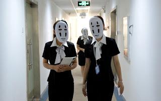 Zdjęcie chińskich pracownic w maskach boga bez twarzy