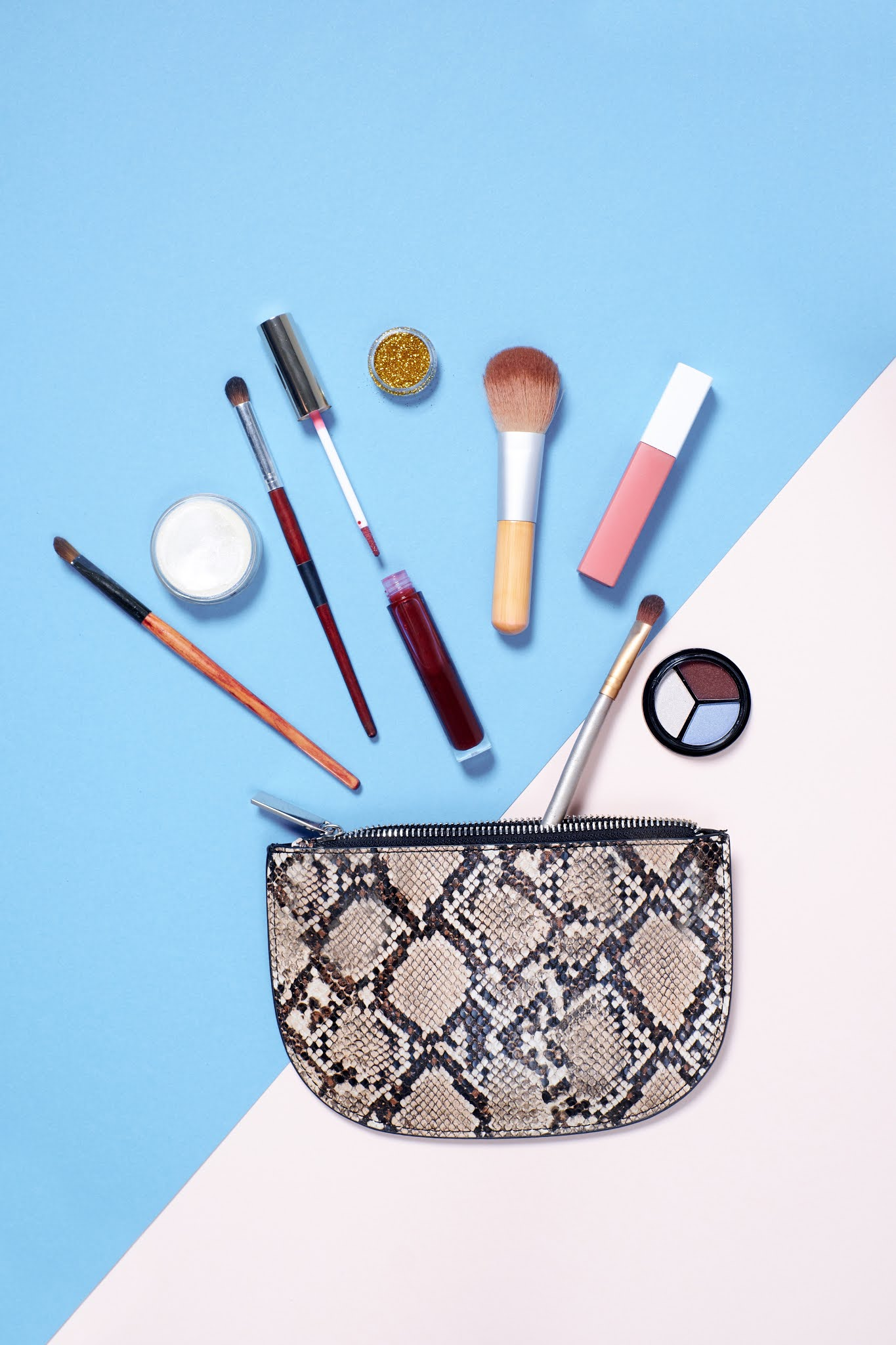 pouch with makeup items falling out of it on blue and white background