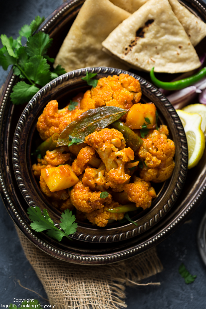 indian aloo gobi served with roti in a metal plate