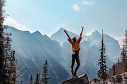 A joyful women on the edge of a mounting feeling a sense of achievement and success in life