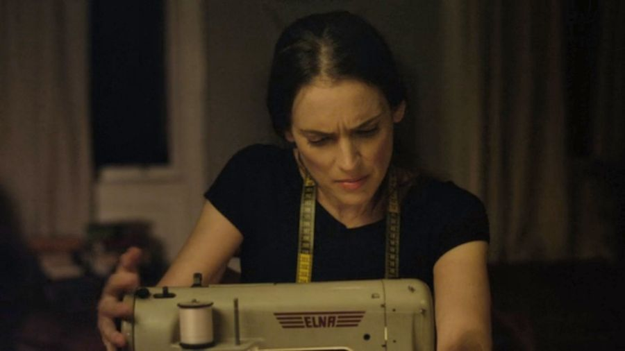 Winona Ryder seated behind a sewing machine.