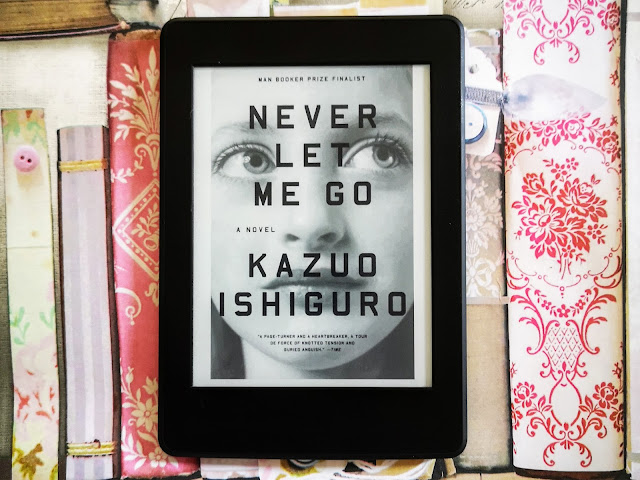 Image of the front cover of the ebook version of Kazuo Ishiguro's novel Never Let Me Go on a Kindle Paperwhite. The cover features and image of a close up of an adolescent girl looking upwards. The Kindle is placed on a floral background.