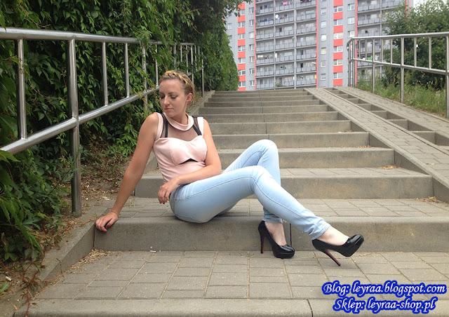 Crop top pudrowy róż, jasnoniebieskie skiny jeans, klasyczne szpilki, brązowy wąski pasek do spodni, warkocz korona