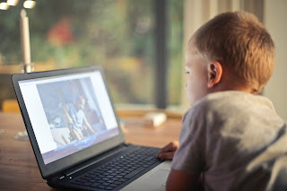 young child looks at a laptop screen with a picture of another young child on it