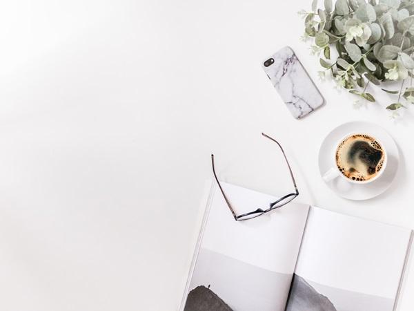 Fundo branco clean imagem óculos, livro e café sobre mesa branca