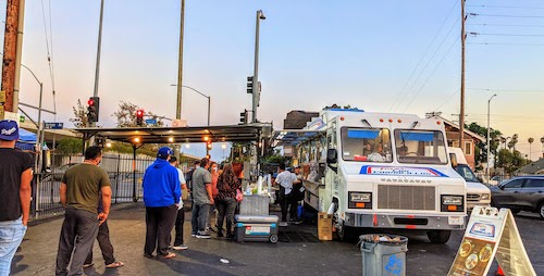 A line of customers at the truck at sunset