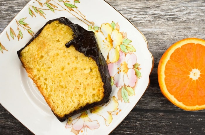 A slice of chocolate topped jaffa orange cake on a floral teaplate