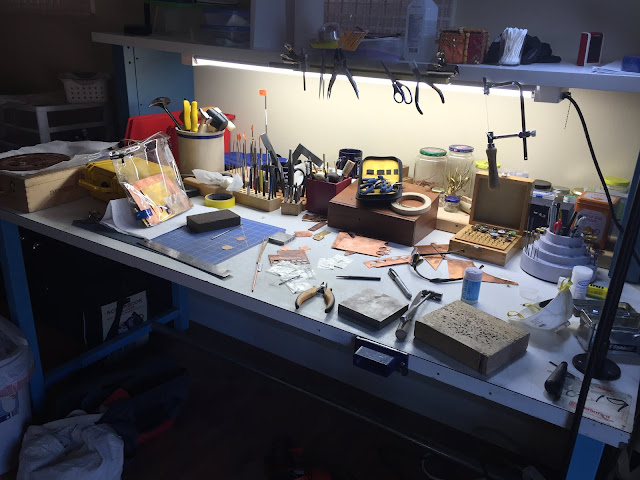 messy bench with metal and tools scattered around