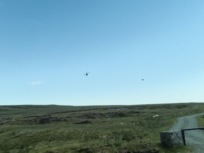 Photo of the North Pennines. In the sky are two dots, which are Chinook helicopters.