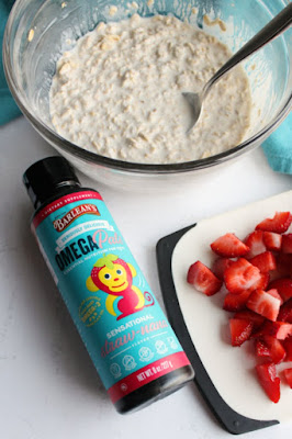 bowl of creamy oat mixture, cutting board with chopped strawberries and bottle of barleans omega pals