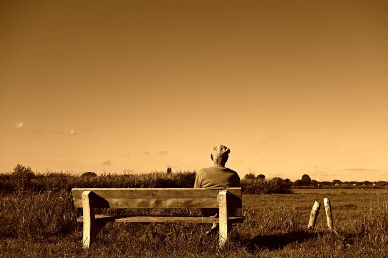 Stary mężczyzna siedzi samotnie na ławce