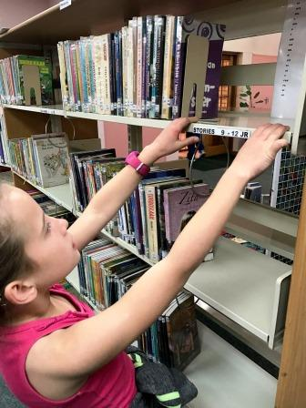 Girl searching for story books on library shelves