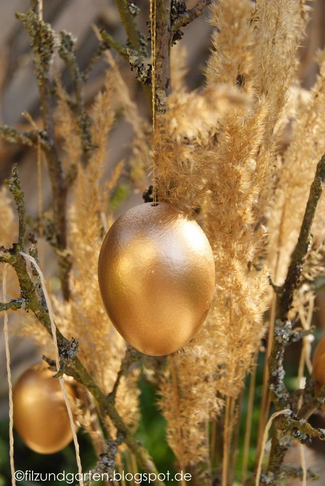 Goldene Ostereier im Gesteck aus Zweigen und Gräsern