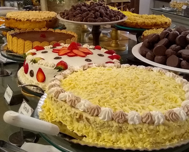 A table with different cakes and other desserts.