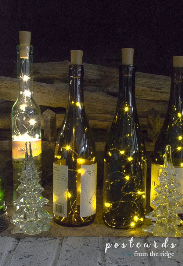 wine bottles with lights and glass Christmas trees inside a fireplace