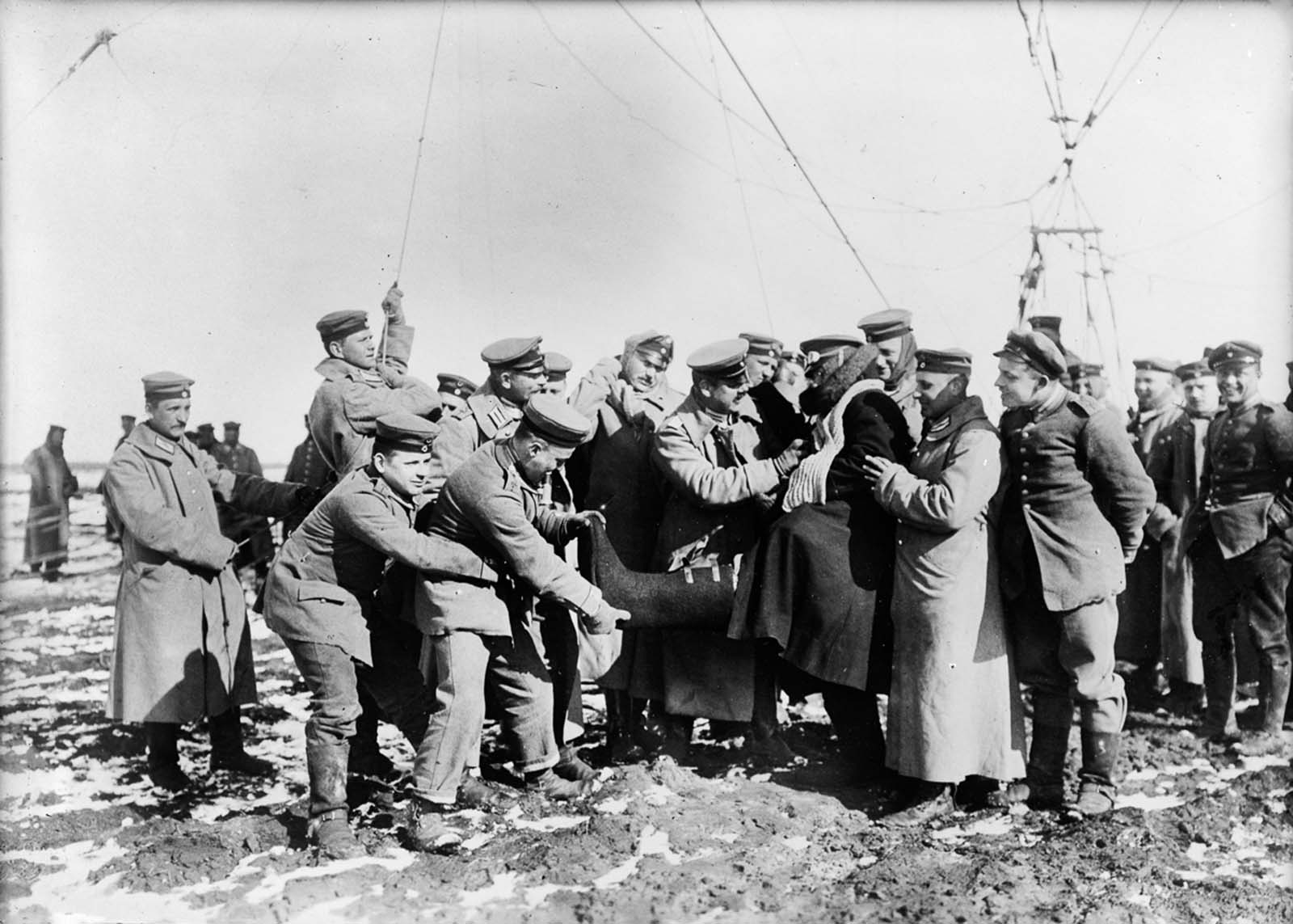 German soldiers help a high-altitude observer remove his heavy clothes. 1915.