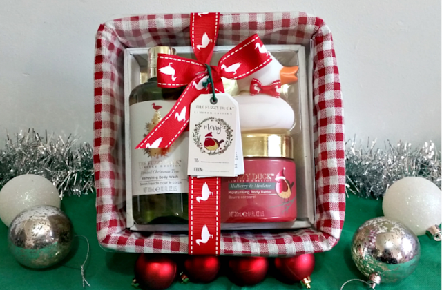 a gift basket containing bottles surrounded by tinsel and red and silver baubles