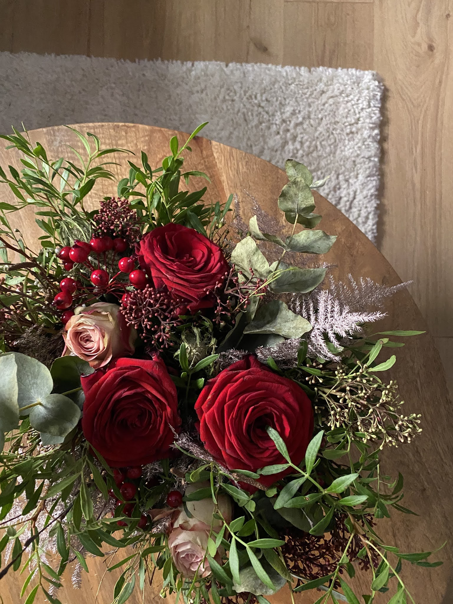 Christmas floral arrangement with red roses, foliage and red berries on a wooden table