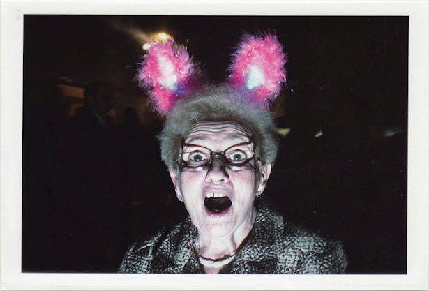 dirty photos - upon - flash street photo of old woman with pink rabbit ears in lisboa