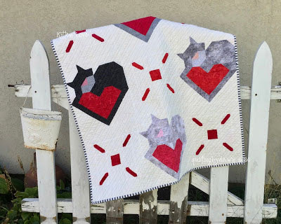grey cats with tails that hug red hearts on a quilt