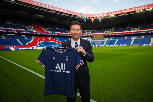 Lionel Messi pictured holding a PSG shirt after signing for the French club