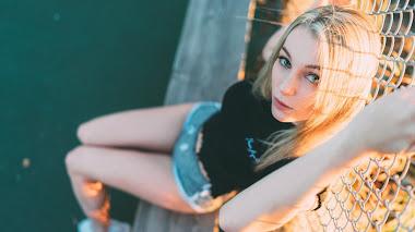 Chica Rubia De Ojos Azules Con Shorts Corto Sentada En Un Muro