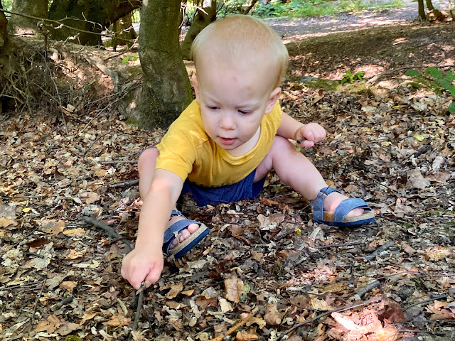 One year old boy sitting on the floor in the forest playing with a stick