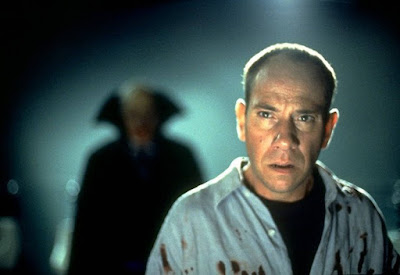 """The Night Flier"" (1997) horror movie still where Miguel Ferrer stands in the middle of an airport full of bodies with a vampire killer right behind him"