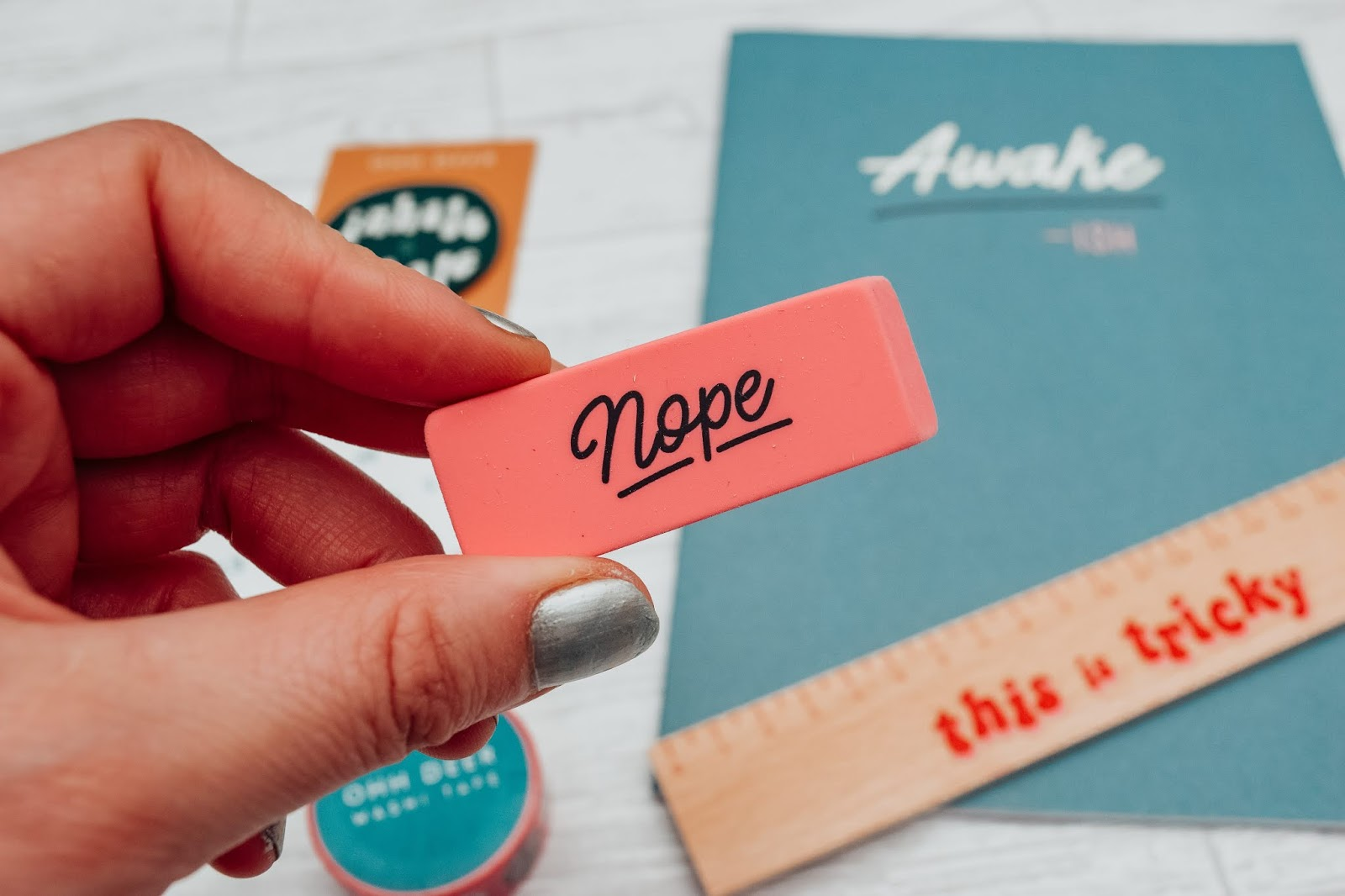 A pink eraser with the word nope printed on it.