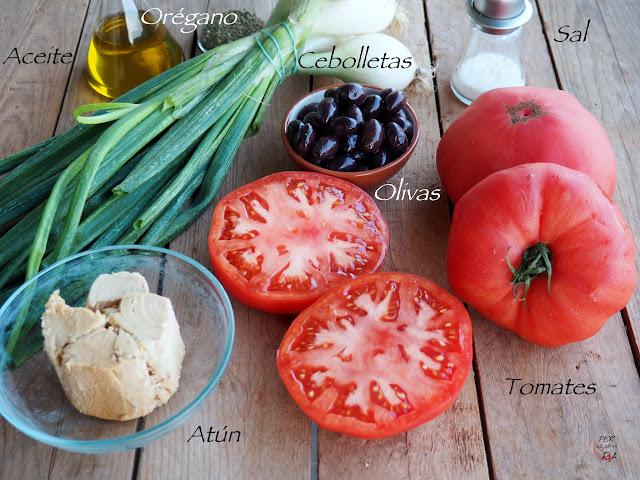 Ensalada que combina gruesas rodajas de tomate maduro, atún en aceite, olivas negras y los tallos verdes de las cebolletas frescas, aromatizado con orégano y aceite de oliva