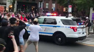 The video shows a New York police truck passing through a crowd during a protest
