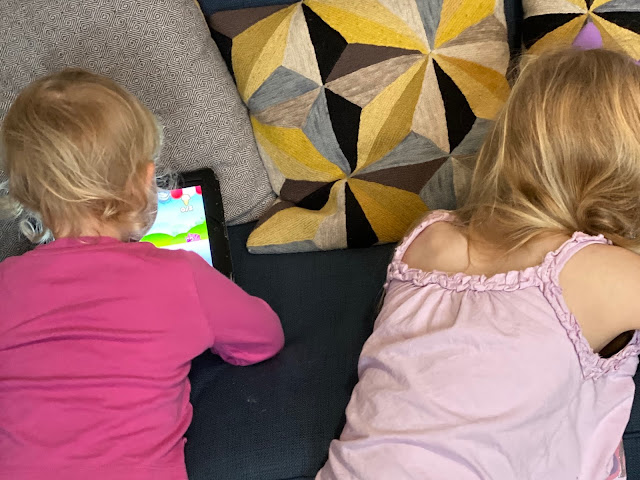 The back of my daughters' heads as they play on an ipad and iphone in their PJ's