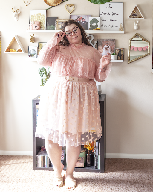 An outfit consisting of a sheer neckline pastel pink micro polka dotted blouse with ruffled tiers tucked into a pastel pink skirt with a sheer pink overlay with pastel pink rosettes and pink slide sandals.