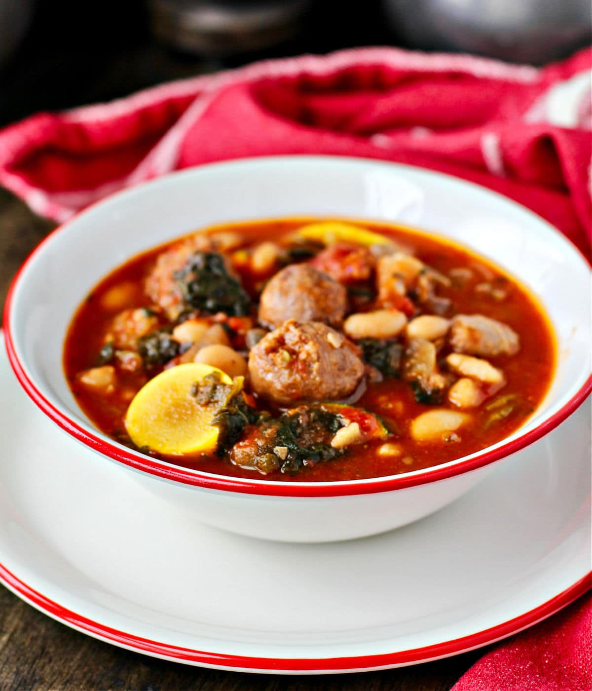 Sausage, Vegetable, and Bean Soup in a bowl with a red rim.