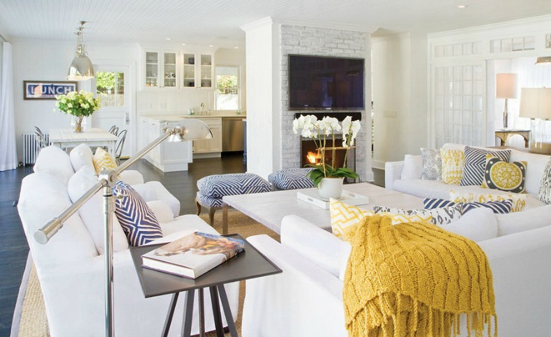 White slipcover sectional sofas and chairs with yellow and navy accents in this coastal beach house