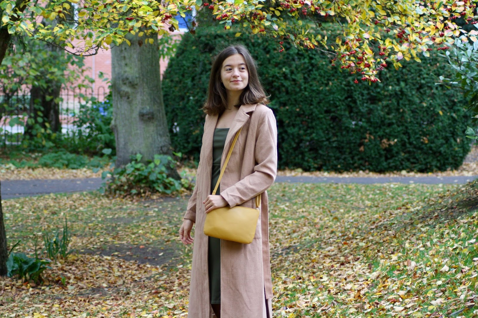 brunette woman standing amongst autumn trees, wearing brown jacket and khaki dress