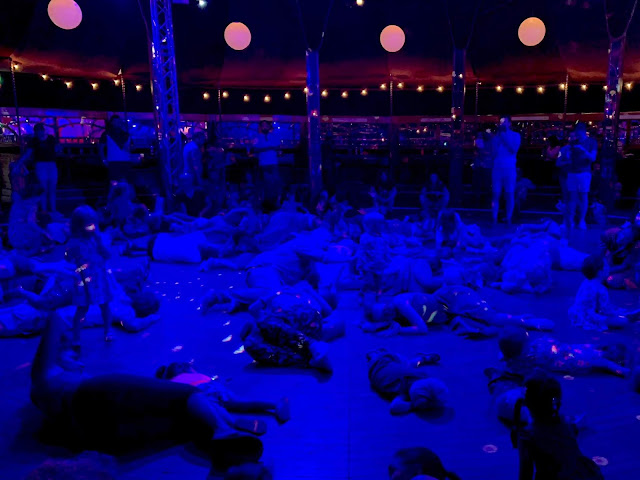 Adults and children on the floor being sleepy bunnies in a dance hall with dark lighting