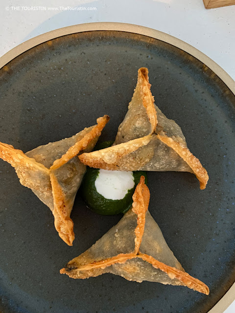 Three Spinach Pies and jogurt sauce in the form of a Japanese dumpling on a black plate