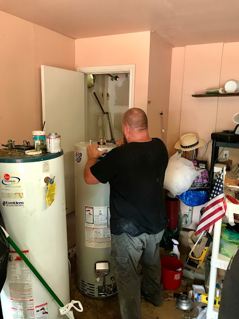 A plumber stands with a new tanked water heater, about to install it in a garage closet. The old heater waits nearby for removal.