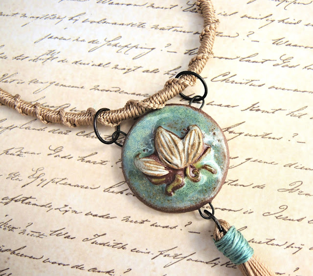 Ceramic lotus pendant by Gaea on a macrame cord.