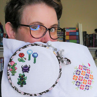Sarah, a 30 year old white woman, holding aida (cross stitch fabric) on an embroidery hoop in front of her face. There is in progress cross stitch of Stardew designs on the section held by the hoop, including flowers, plants and Junimos (forest spirits in game). On the other side of the fabric is a floral design.