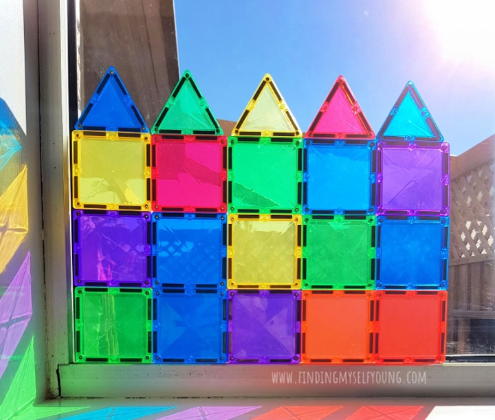 magnetic tiles on a window to create a stained glass window.