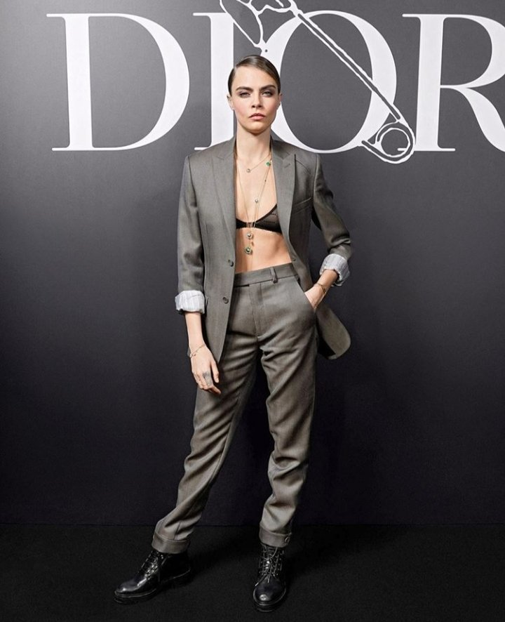 Cara Delevingne looked sensational in a semi-sheer bra and a grey blazer at Dior Homme fashion show in Paris