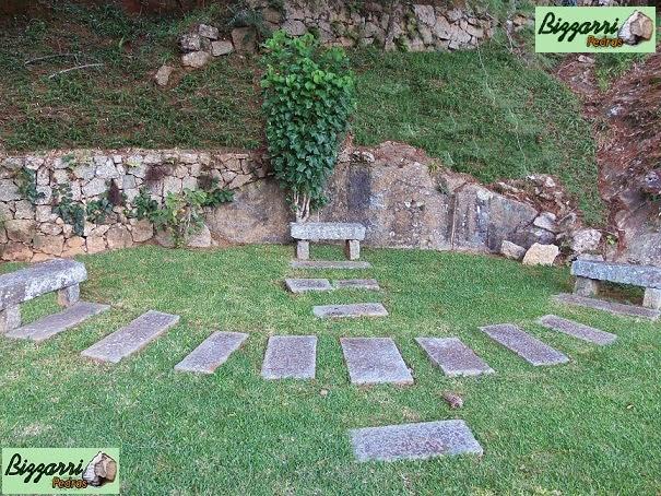 Caminho com pedras folheta com o muro de pedra rústica com os bancos de pedra folheta e a execução do paisagismo natural.