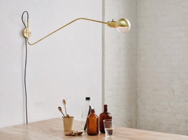 Wandlampe mit Schwengarm und Messing über einem Tisch