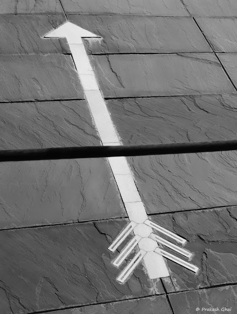 A Black and White Minimalist Photo of a White Arrow being cut by a Black wire at Jawahar Kala Kendra, Jaipur.