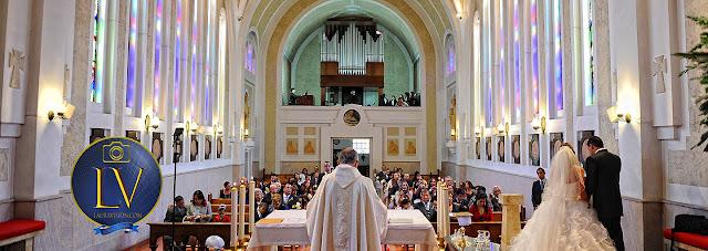 Cura y novios de espaldas leyendo en la misa delante de los invitados