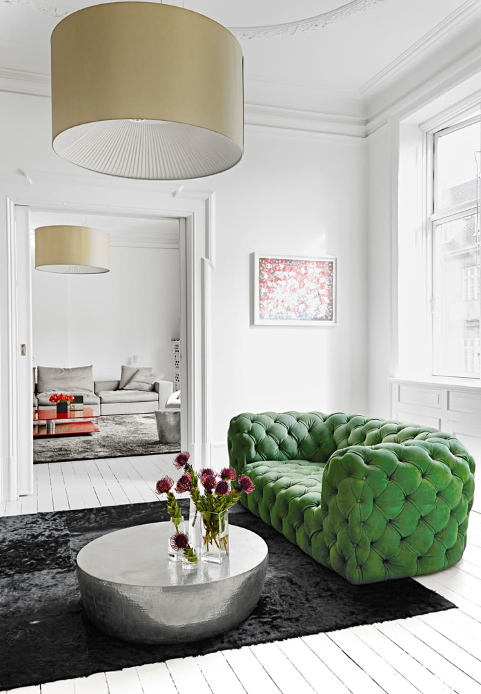 That gorgeous green chesterfield sofa steals the show in this living room.