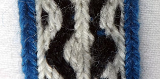A section of tablet woven band with the weft passing over a thread it should be under