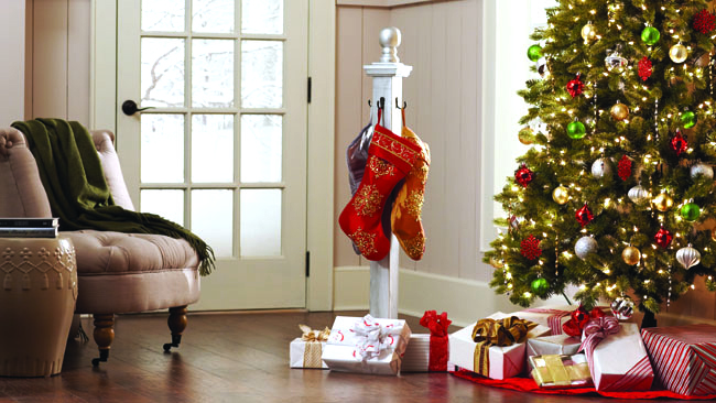 living room with christmas tree, chair, gifts and stocking holder by the side of of the door with mullions